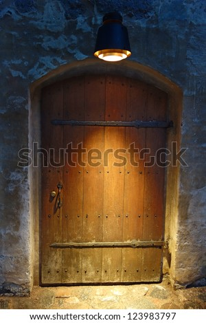 Old wooden door in Turku castle, with lamp above - stock photo