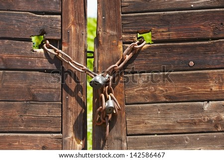 Old wooden door locked with chain and padlock. - stock photo