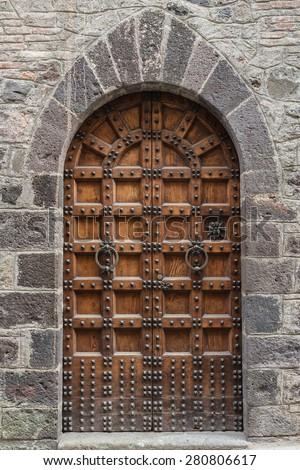 old wooden door of a broken brick wall - stock photo