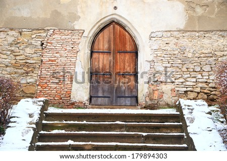 Old wooden door to a cathedral in Transylvania - stock photo