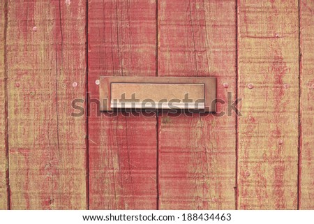 Old wooden door with a brass letterbox - stock photo
