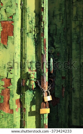 Old wooden door with green peeling paint and padlocks - stock photo