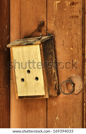 Old wooden door with mailbox hanging - stock photo