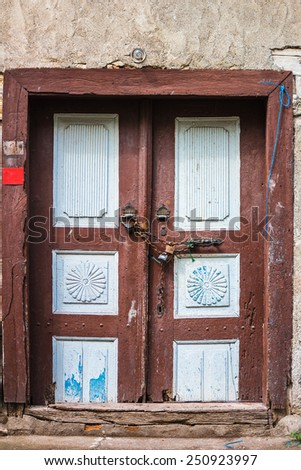 Old wooden door with metal hinges and lock - stock photo
