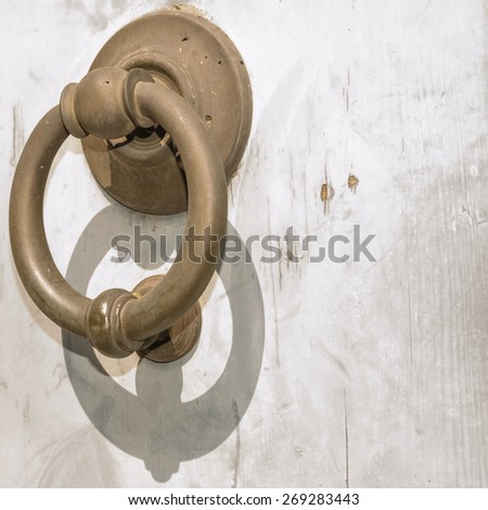 Old wooden door with ring knockers, of brass - stock photo