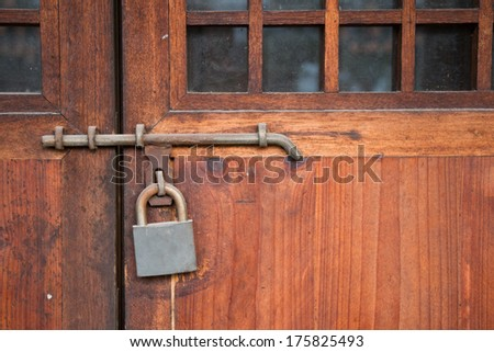 Old wooden door with rustic lock - stock photo