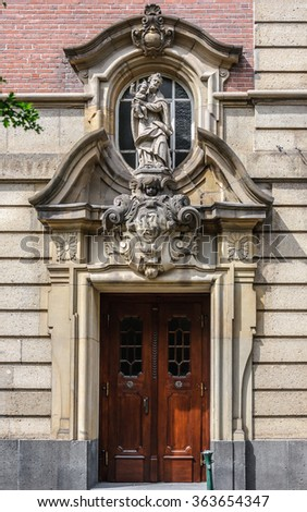 Old wooden door with statue in the Basilica of St. lambertus (St. Lambertus Church) is the Roman Catholic Church, which is still in effect, Dusseldorf, Germany - stock photo