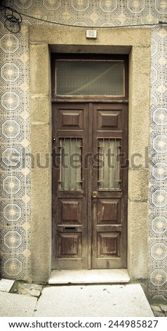 Old wooden door with window on the wall with ceramic tile. Toned. - stock photo
