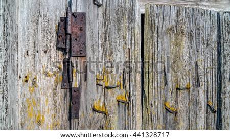 old wooden door with wrought iron hinge - stock photo