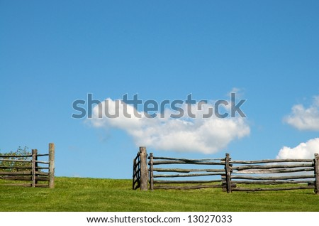Old wooden fence and open gate and green pasture against blue sky filled with clouds - stock photo