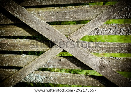 Old wooden fence covered with moss. Behind the fence the green field .  - stock photo