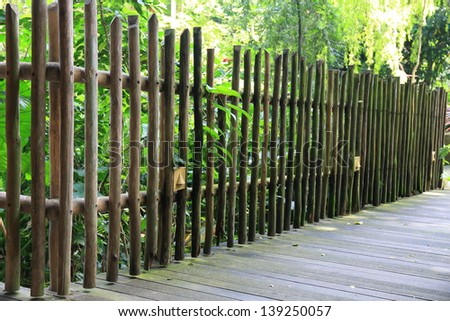 Old wooden fence in garden. - stock photo