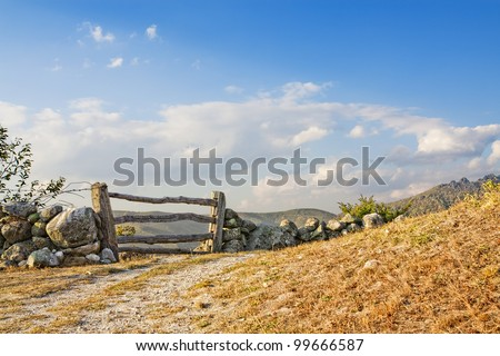 Old wooden fence in stone rock wall - stock photo