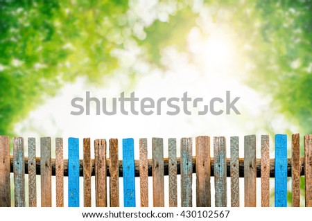 Old wooden fence on blurred nature background. - stock photo