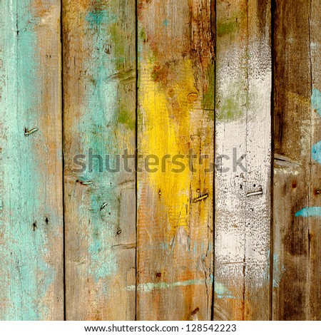 Old wooden fence painted in different colors - stock photo