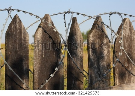 Old wooden fence with barbed wire closeup photo - stock photo