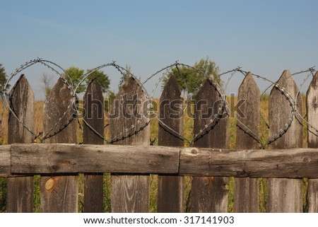 Old wooden fence with barbed wire photo - stock photo