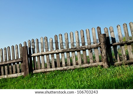 Old wooden fence with grass and sky - stock photo