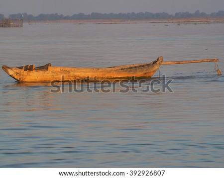 old wooden fishing boat on the lake in sunset - stock photo
