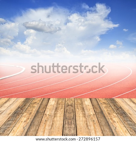 Old wooden floor at curve of a running track and blue sky background - stock photo