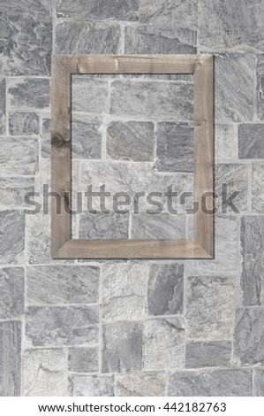 Old wooden frame on stone wall background of interior decoration. - stock photo