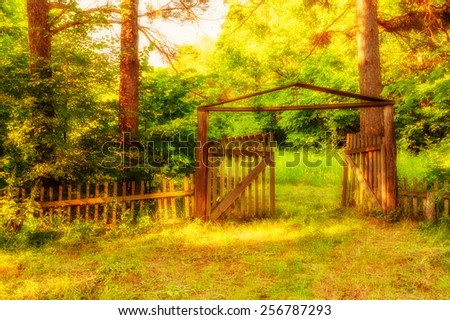 Old wooden gate with cross at top in forest - stock photo
