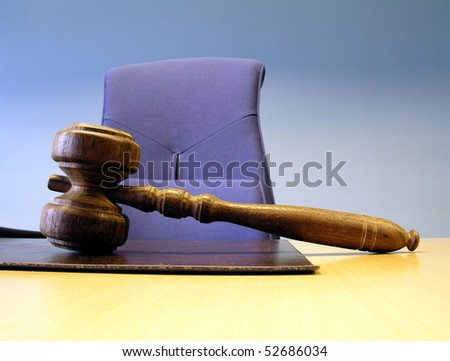 Old wooden gavel isolated on a office table with a chair - stock photo