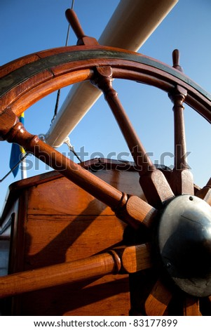 Old, wooden helm on blue sky. Navigation - stock photo