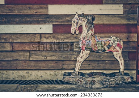 old wooden horse with old wood background - stock photo