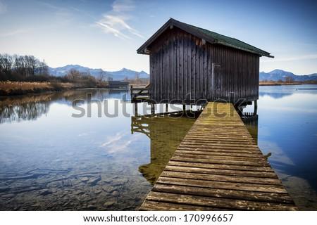 old wooden hut at a lake - stock photo