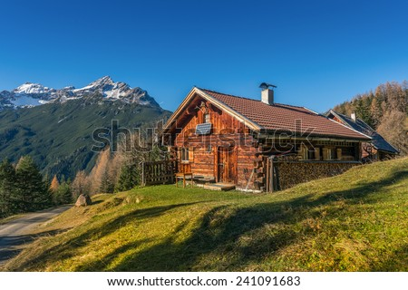 old wooden hut cabin in mountain alps at rural fall landscape - stock photo