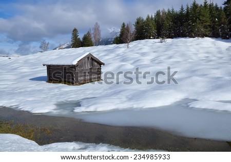 old wooden hut on snowy alpine meadow, Germany - stock photo