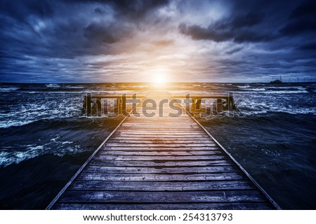 Old wooden jetty during storm on the ocean. Abstract light at the end. Concept of hope, future, religion, god etc. - stock photo