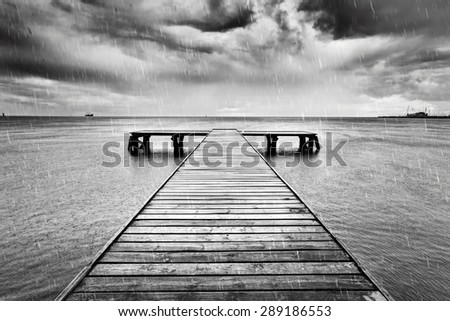 Old wooden jetty, pier on the sea. Raining from dramatic sky with dark, heavy clouds. Black and white - stock photo