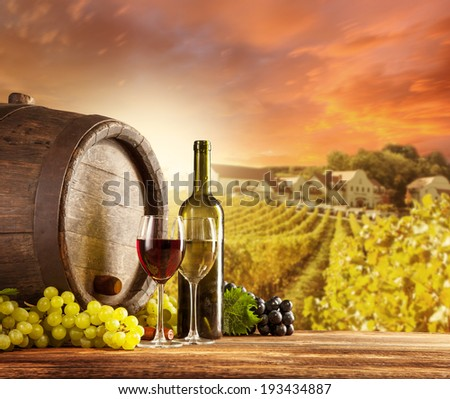 Old wooden keg with bottle and glass of red, white wine. Rural vineyard on background - stock photo
