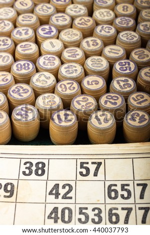 Old wooden lotto barrels and cards as background (soft focus). - stock photo