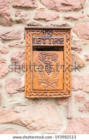 Old wooden mailbox decorated with grape pattern on a stone wall - stock photo