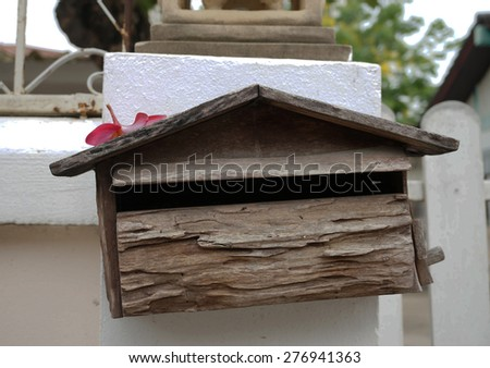 Old wooden mailbox, house shape placed on white wall background.                             - stock photo