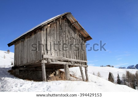 old wooden mountain hut in the snow - stock photo