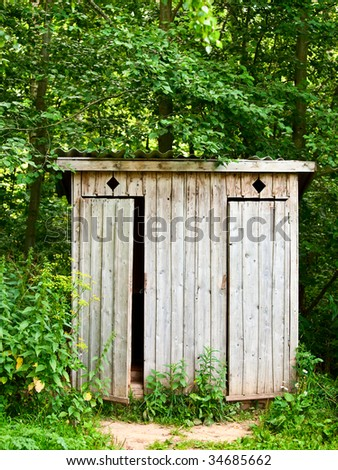 Old wooden outhouse in the forest - stock photo