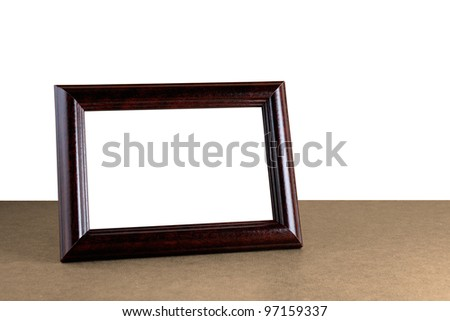 Old wooden photo frame on table isolated on white background - stock photo