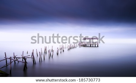 Old wooden pier. Long exposure in Carrasqueira Palaphitic pier, near Lisbon, Portugal - stock photo