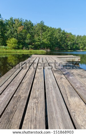 Old wooden pier on small local lake. - stock photo