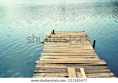 Old wooden pier on the lake. - stock photo