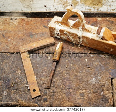 Old wooden plane, elbow, chisel on dirty table, struck by termites. old woodworking tools. top view - stock photo