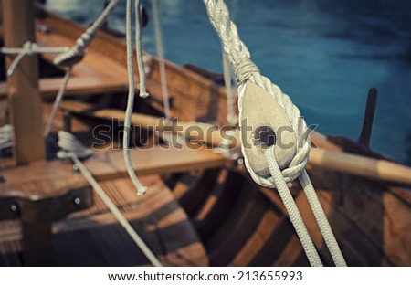 Old wooden sailboat pulleys and ropes detail. Selective focus and shallow depth of field.  - stock photo