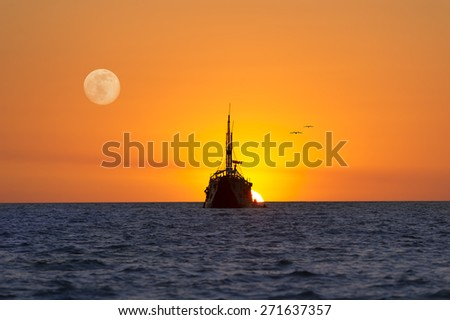Old wooden ship sits at sea as the sun sets and the moon rises like a fantasy. - stock photo