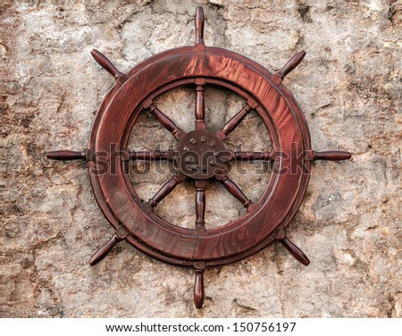 Old wooden ship steering wheel on stone wall - stock photo