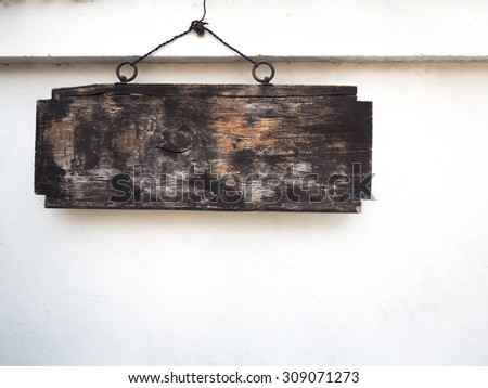 Old wooden sign hanging on wall - stock photo