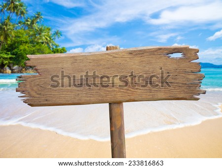 old wooden signboard on tropical beach - stock photo